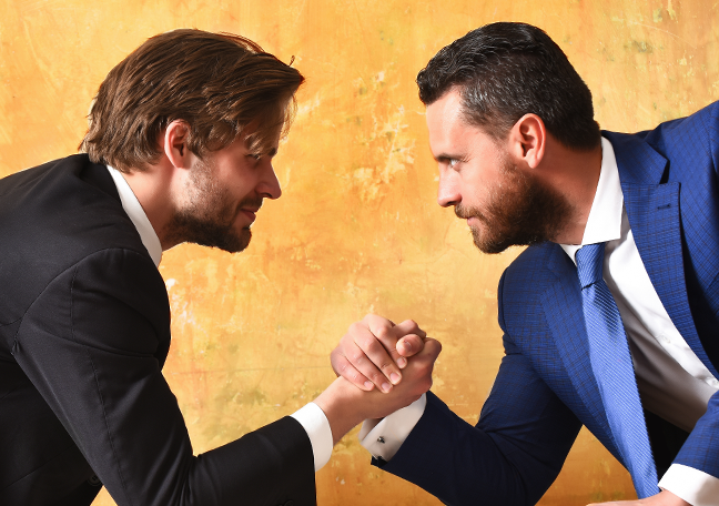 coworkers arm wrestling showing employee rivalry