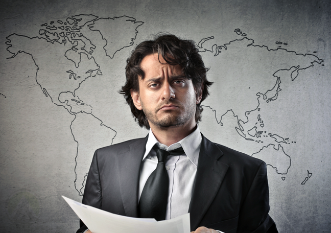 worried businessman holding paper with world map backdrop