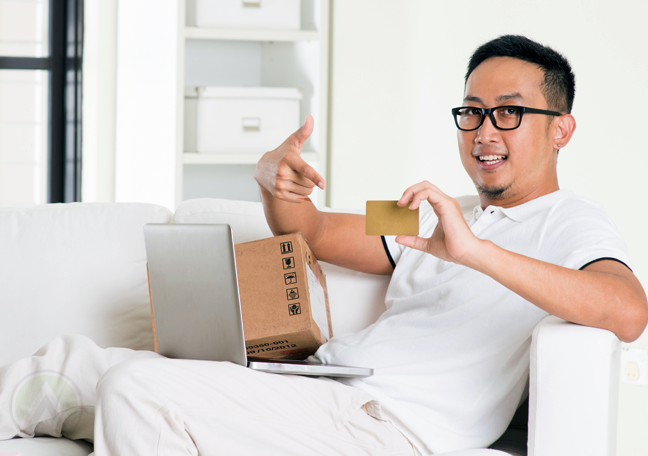 chinese man in white sitting in couch with laptop box delivery pointing to credit card