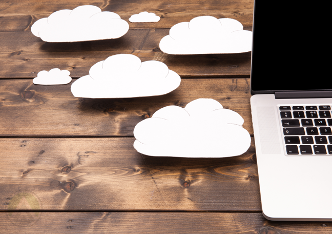 clouds coming out of laptop on table showing cloud computing concept