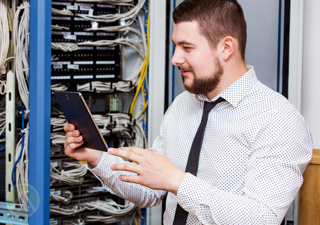 it manager looking at tablet inspecting server