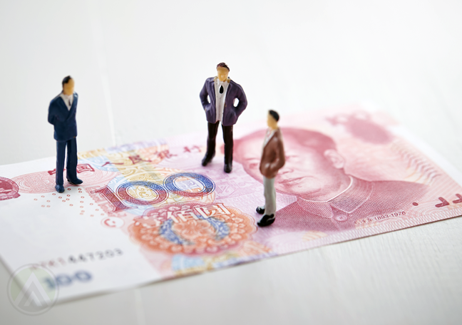 miniature businessmen standing on Chinese banknote money