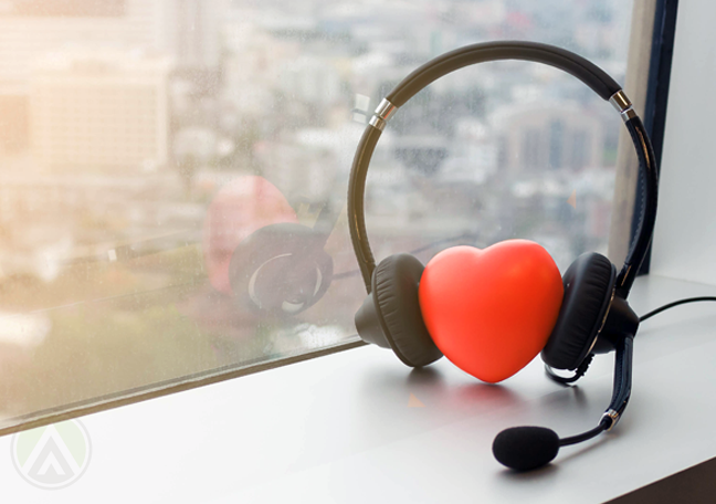 rubber heart wearing customer service headset by window