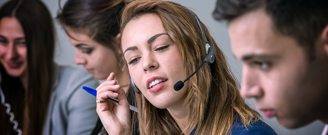 busy call center agent speaking to caller surrounded by customer service coworkers