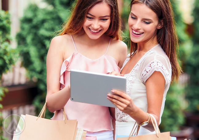 friends looking at tablet holding shopping bags