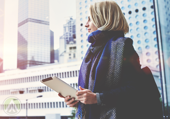 woman contemplating standing outdoors by building holding tablet