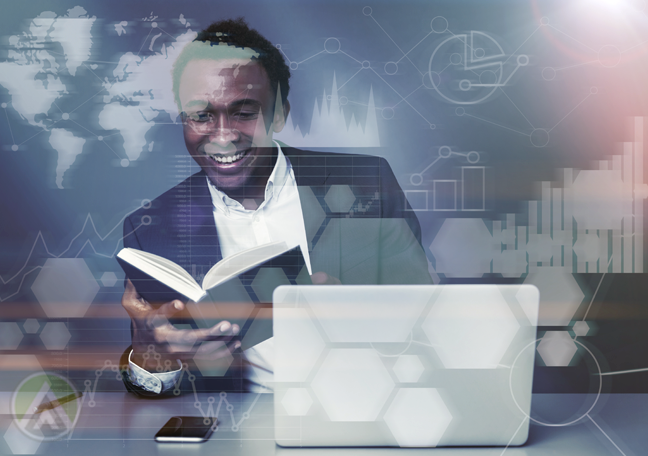 happy smiling young businessman reading book by laptop stats figures charts graphs overlay