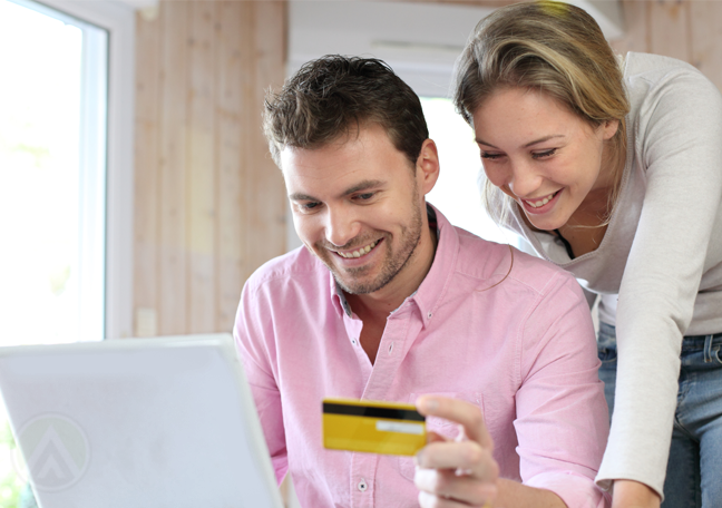 couple looking at laptop holding credit card doing online shopping ecommerce