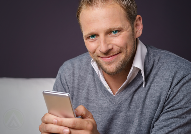 man smiling brightly with smartphone