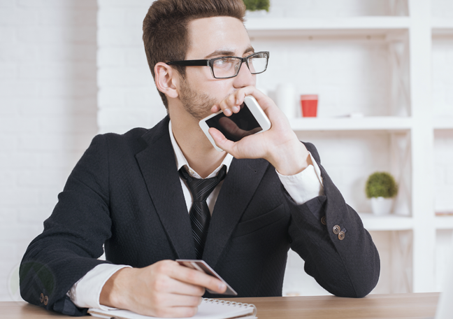 businessman in glasses thinking holding smartphone credit card