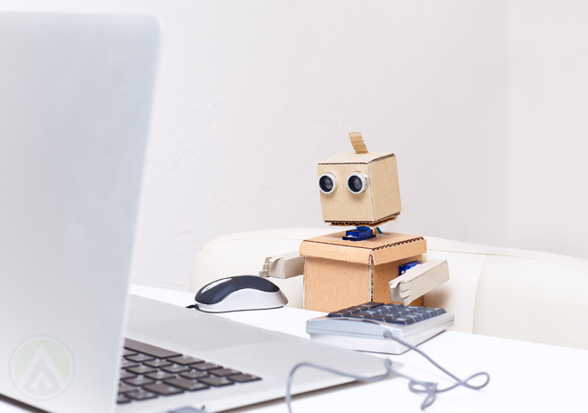 small robot using phone by laptop computer