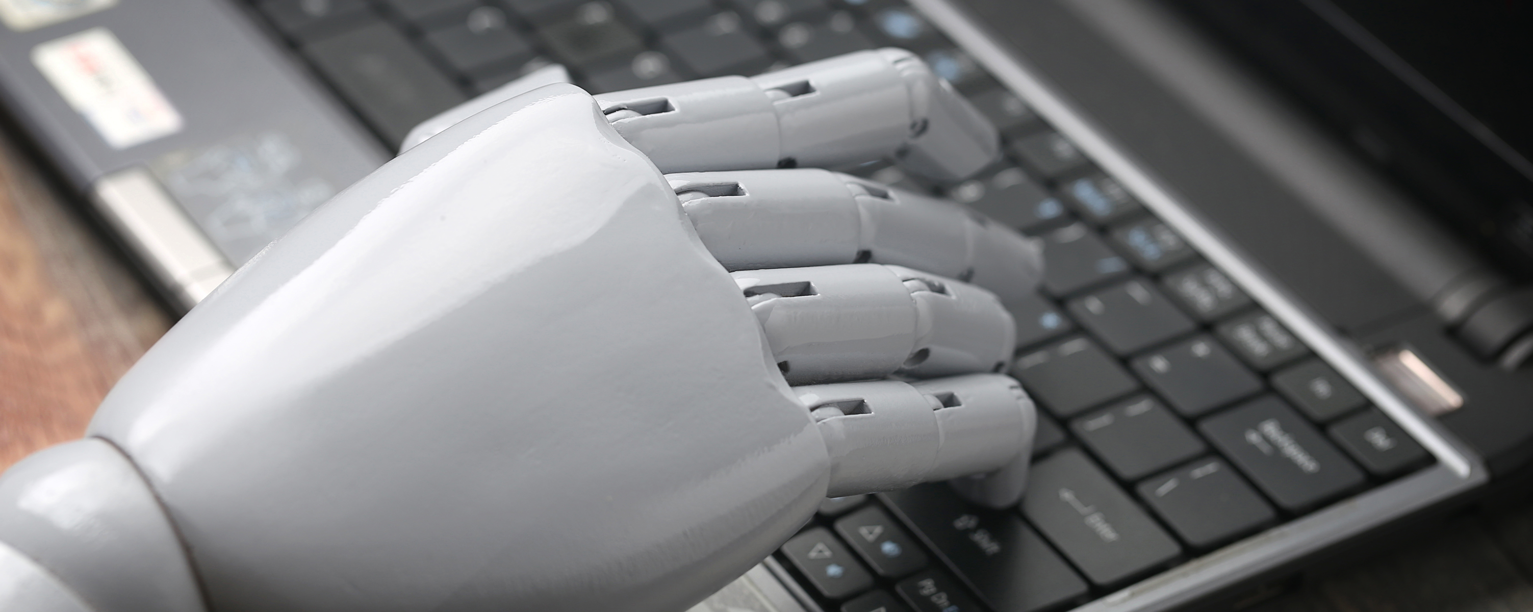 sleek white robotic hand resting on laptop computer keyboard_Open Access BPO